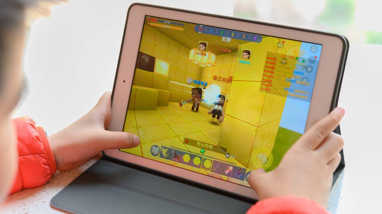 Criança segurando tablet enquanto constrói casas Minecraft