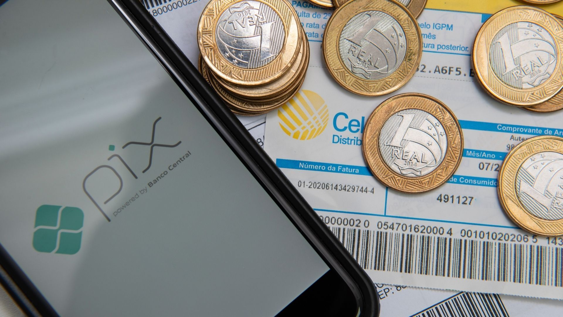 """Celular com os dizeres """"Pix"""" na tela, ao lado de moedas de um real e em cima de boletos bancários"""