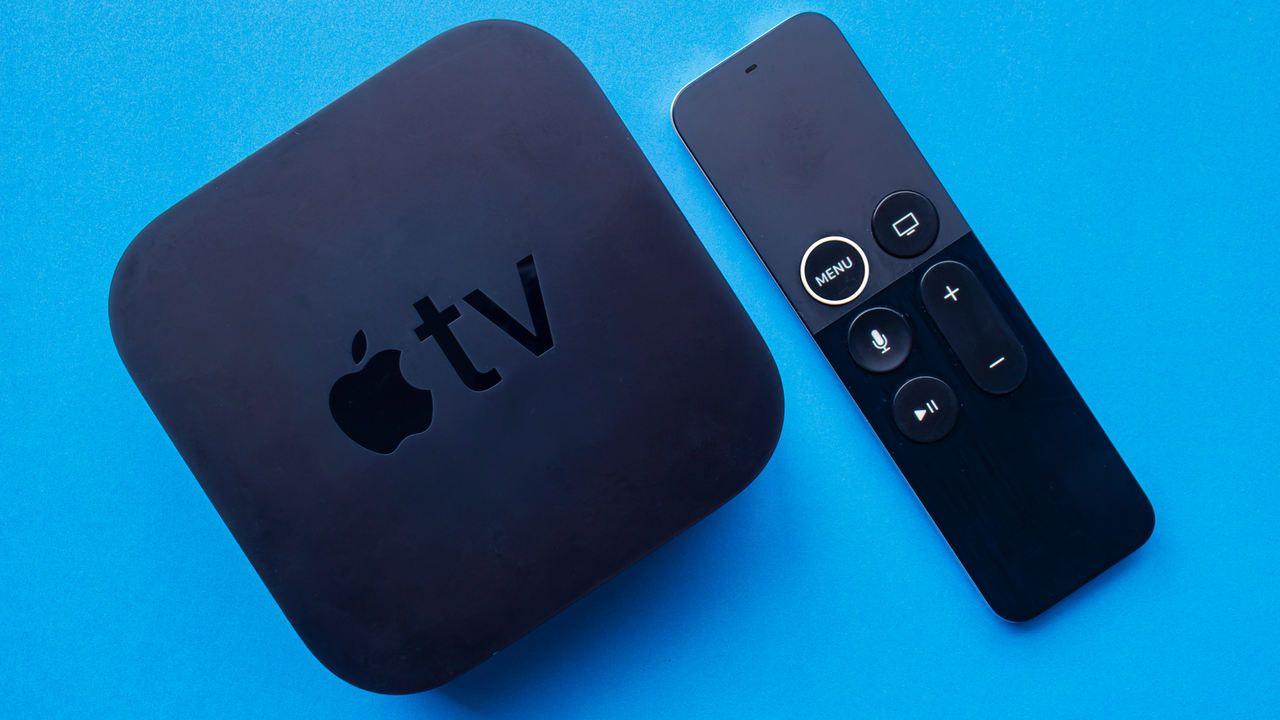 Apple TV ao lado de seu controle remoto, ambos apoiados sobre superfície azul clara.