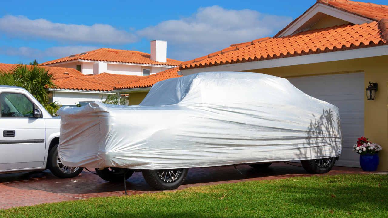 Grande carro coberto por capa cinza em frente a garagem de casa amarela
