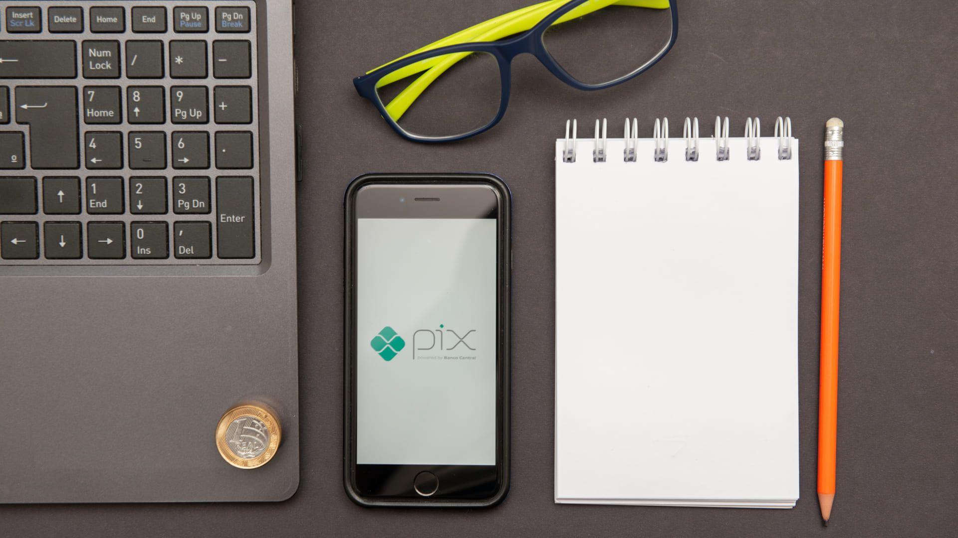 """Mesa com notebook, celular (com os dizeres """"Pix""""), óculos, bloco de notas e lápis"""