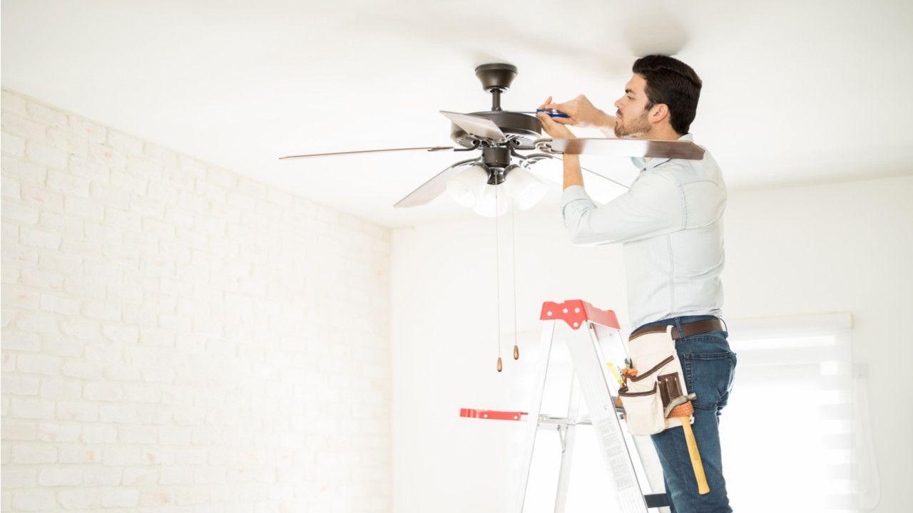 Homem branco em cima de uma escada, fixando um ventilador de teto com uma chave de fenda.