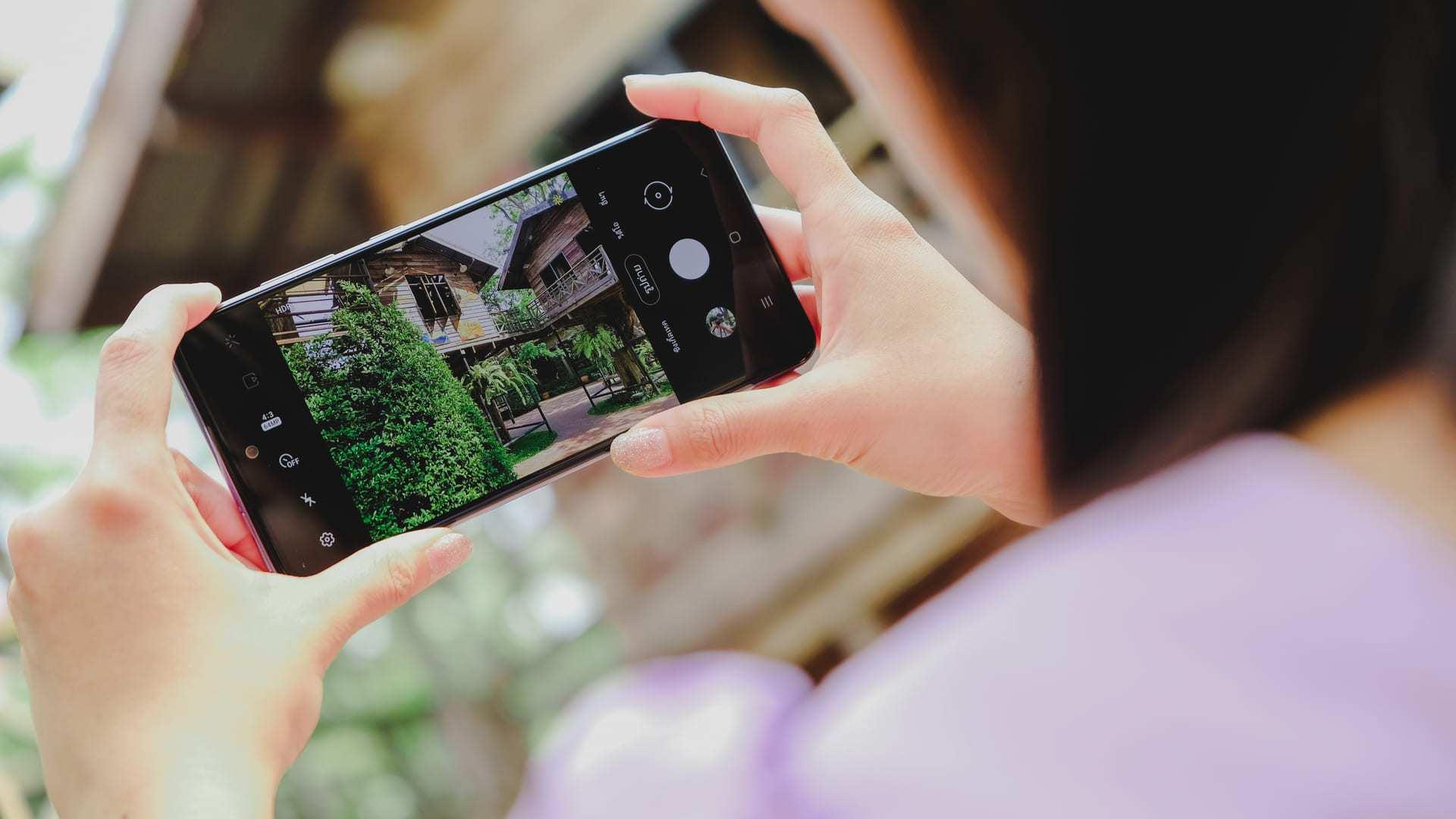 Mãos segurando A52 e usando câmera do celular