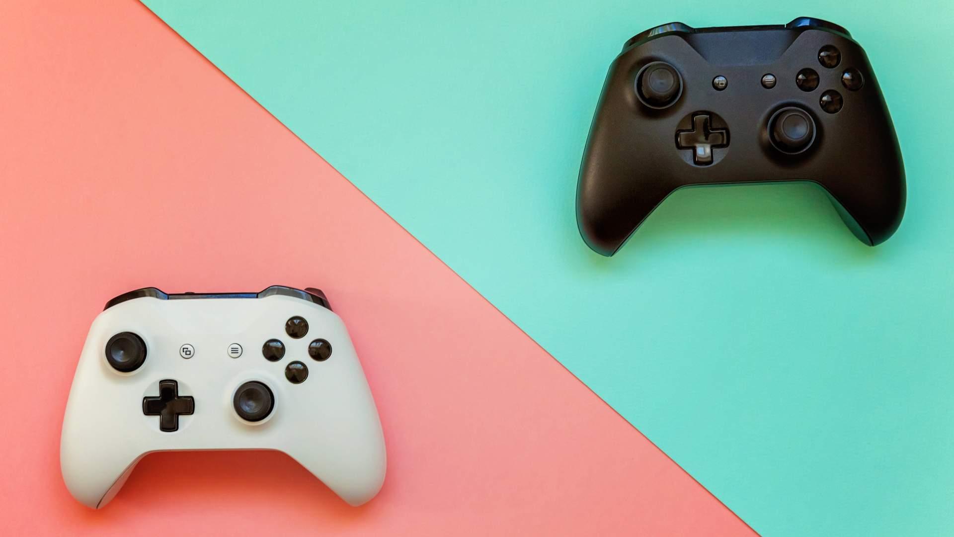 Um controle branco sobre fundo rosa no canto inferior esquerdo e um controle de videogame preto sobre fundo verde no canto superior direito da imagem