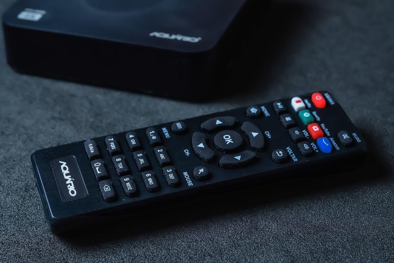 Controle remoto da TV box Aquário, feito de plástico preto e com botões de atalho para Netflix, Spotify, Youtube e Prime Video