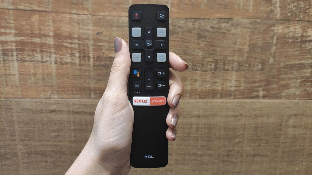 Mão segurando o controle remoto da smart TV TCL P615 de frente