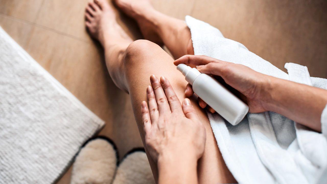 Pernas de uma mulher com uma das mãos apoiadas na coxa e outra segurando um creme.