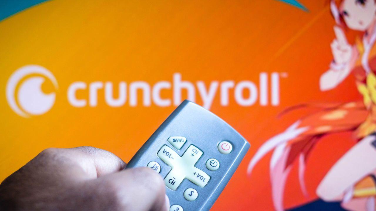 Crunchyroll aberto em uma TV, com controle remoto em primeiro plano apontando para a tela.