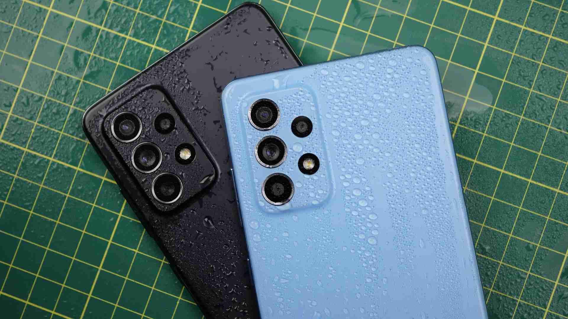 Foto exibe a traseira de dois celulares A52 5G com respingos de água