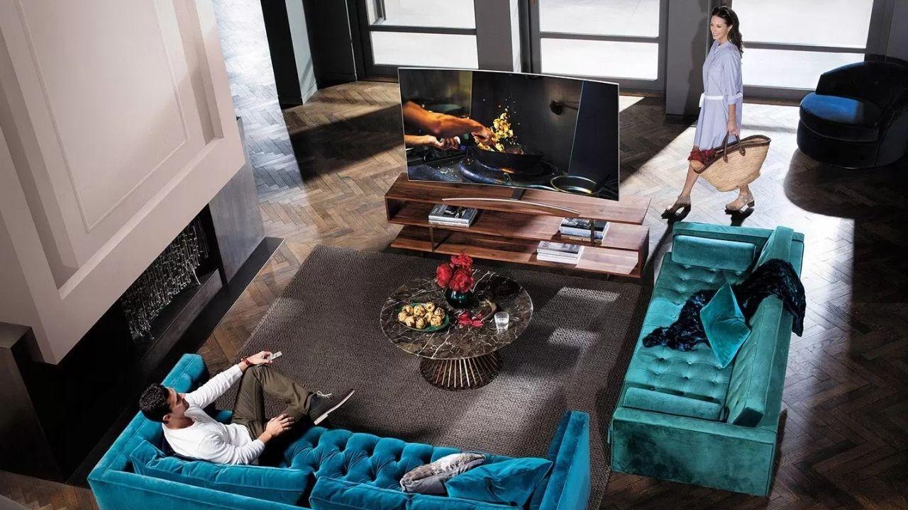 Sala de estar com dois sofás azuis e, sobre um rack de madeira, a TV curva Samsung Q8C.