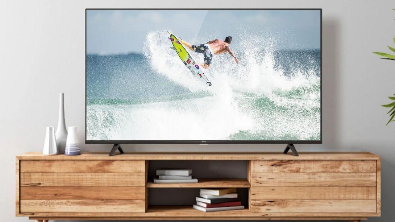 Smart TV TCL P615 exibindo imagem de surfe. A TV está sobre um rack de madeira, com livros na prateleira.