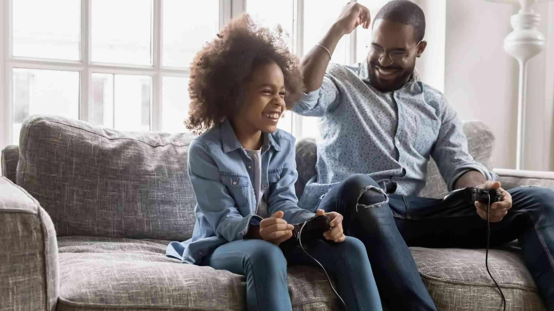 Homem e menina negros jogando videogame e comemorando