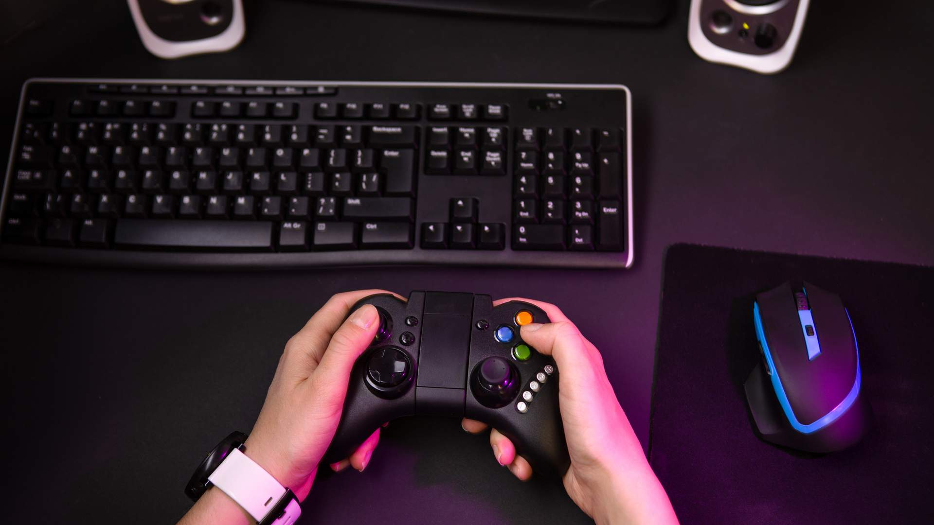 Mesa preta com teclado, mouse e controle de videogame sendo segurado