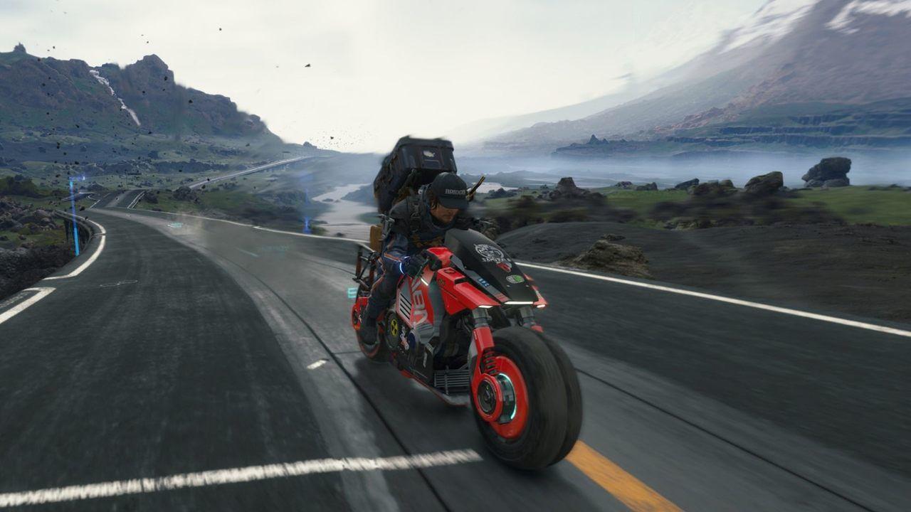 Cena do jogo Death Stranding, com o personagem Sam dirigindo uma moto em alta velocidade em uma estrada asfaltada