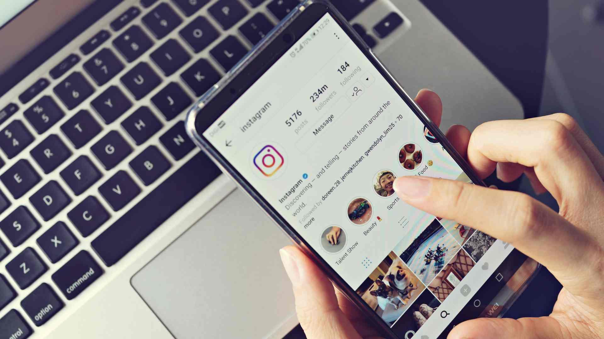 Mãos segurando celular com Instagram aberto na página de perfil do usuário, com um notebook ao fundo