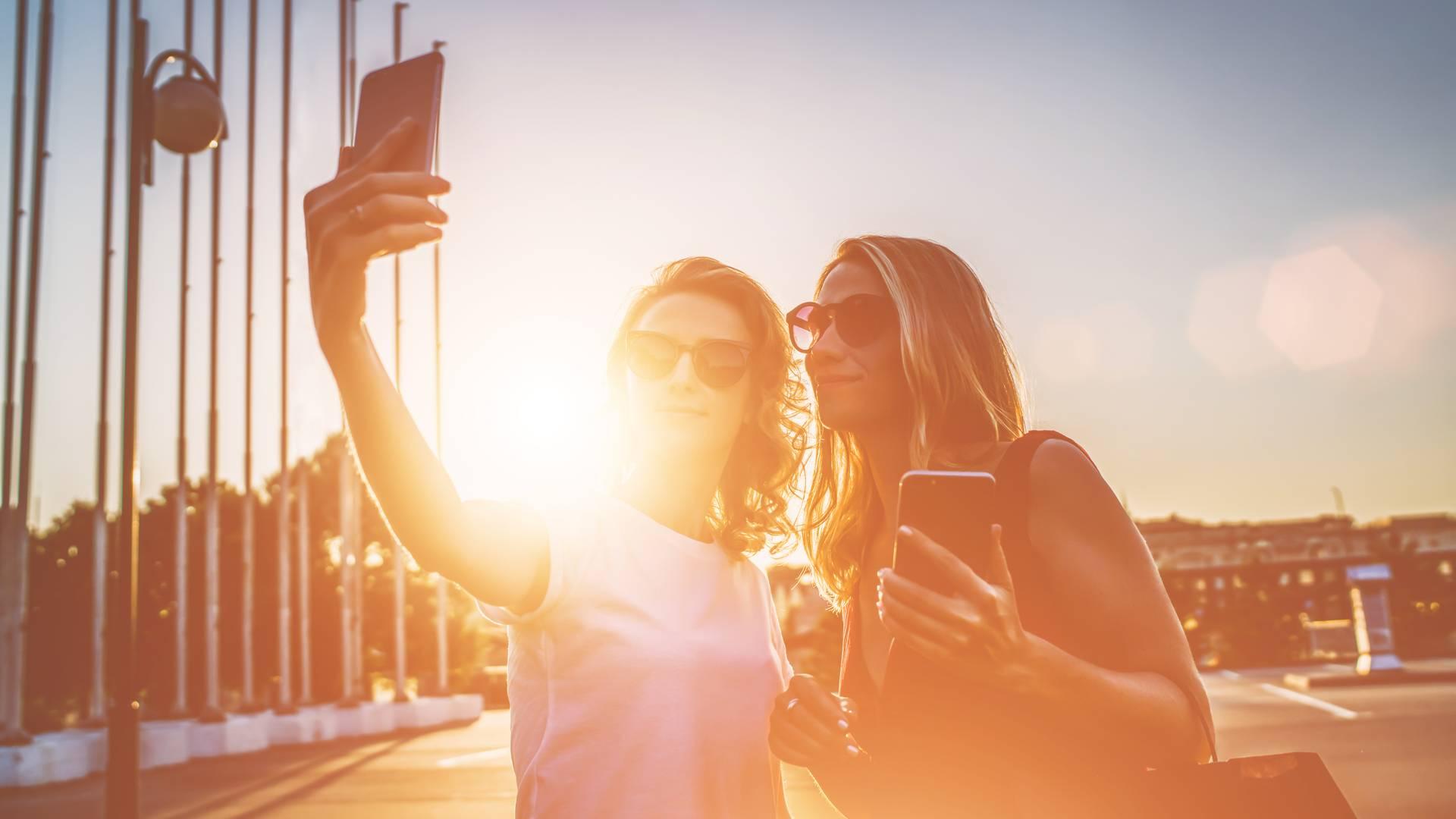Duas mulheres jovens de óculos escuros tirando uma selfie com o celular em um dia de sol