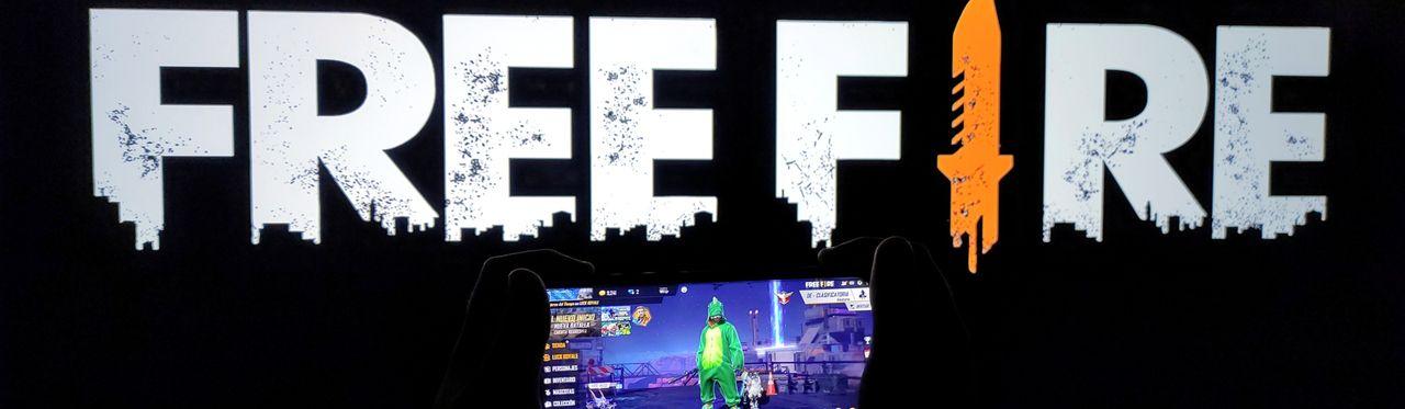 Free Fire aberto na TV em segundo plano, com celular também aberto no jogo em primeiro.