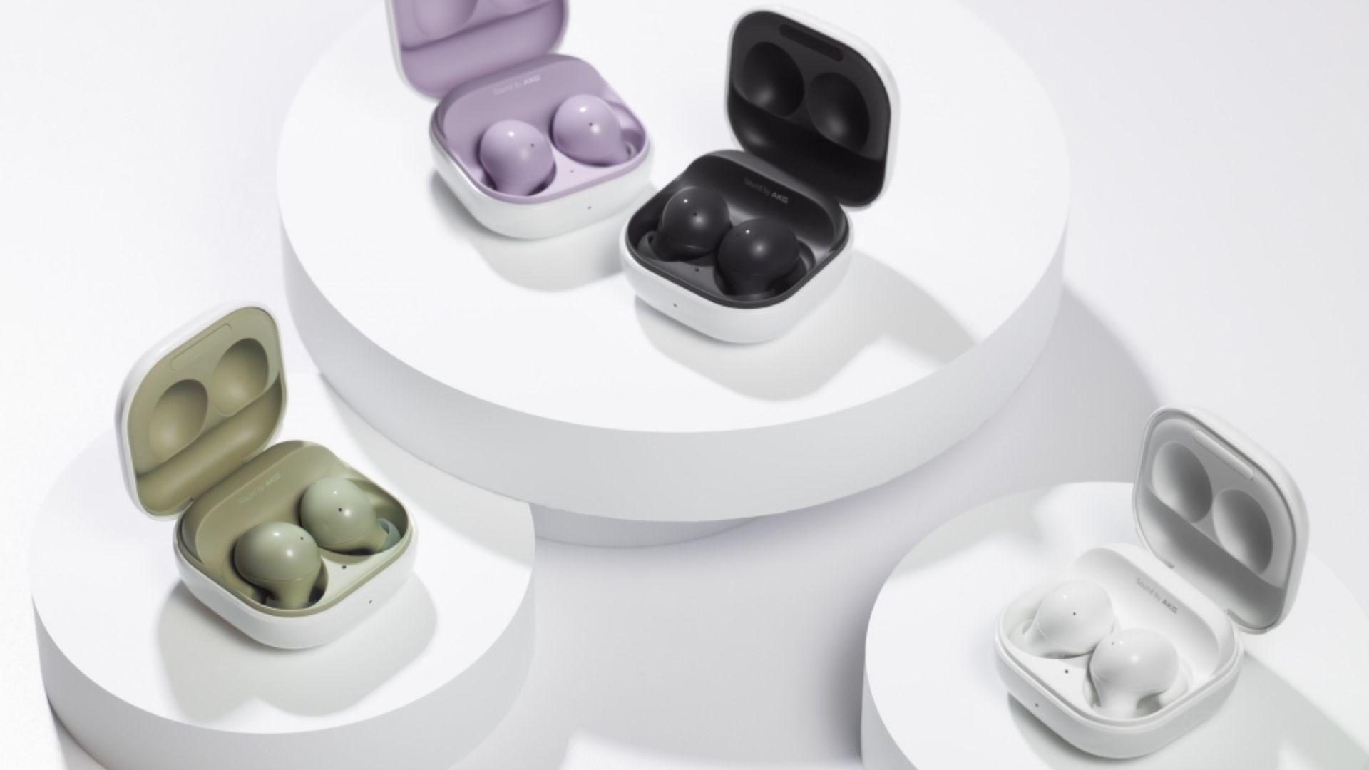 Quatro fones Galaxy Buds 2 nas cores verde, violeta, preto e branco em fundo branco e com cases abertas