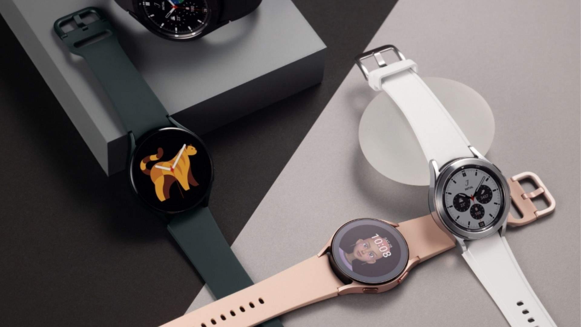 Três modelos de Galaxy Watch 4 nas cores preto, rosa e branco apoiados em uma mesa