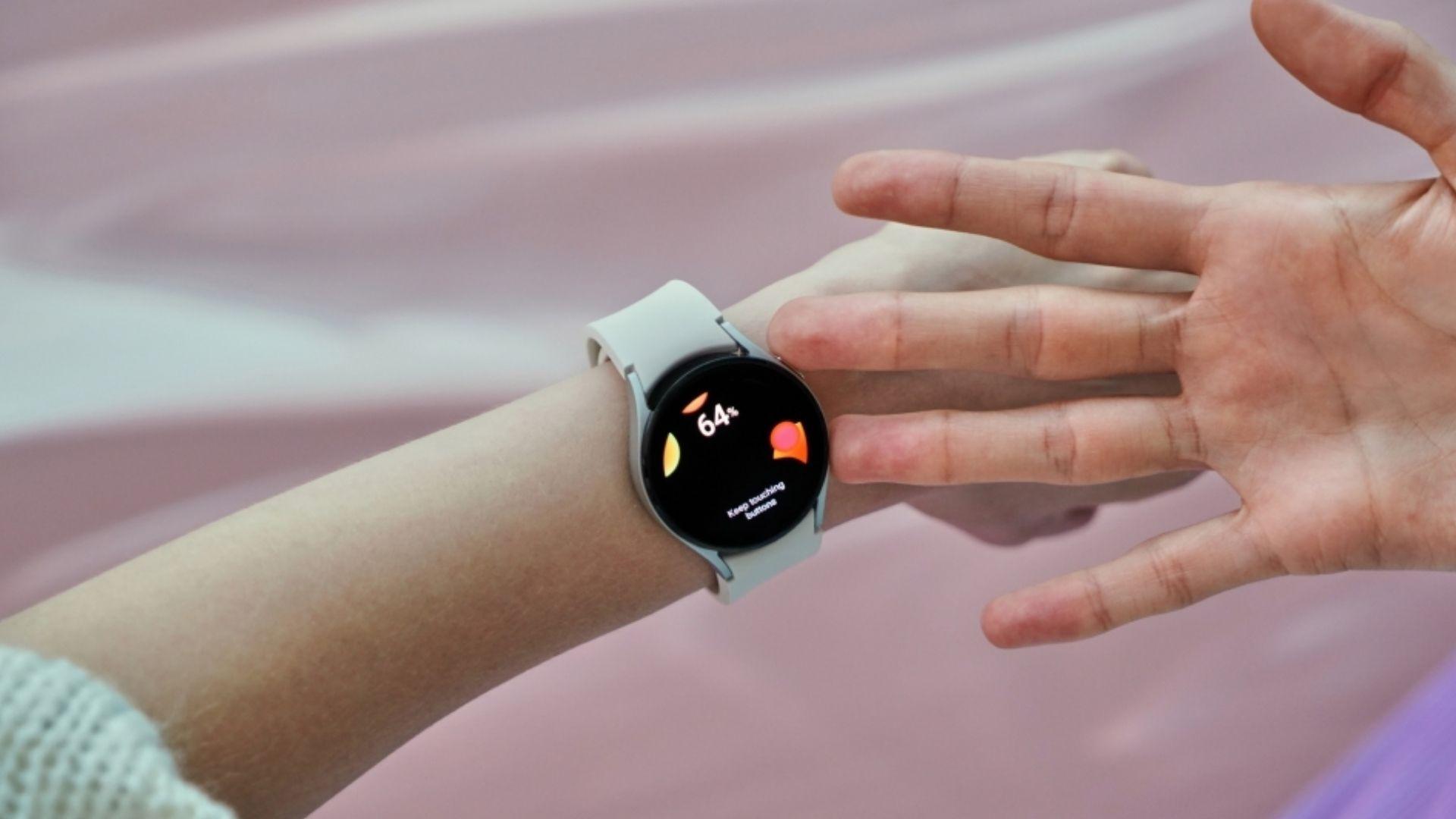 Pessoa com Galaxy Watch 4 no pulso com os dedos apoiados nos sensores