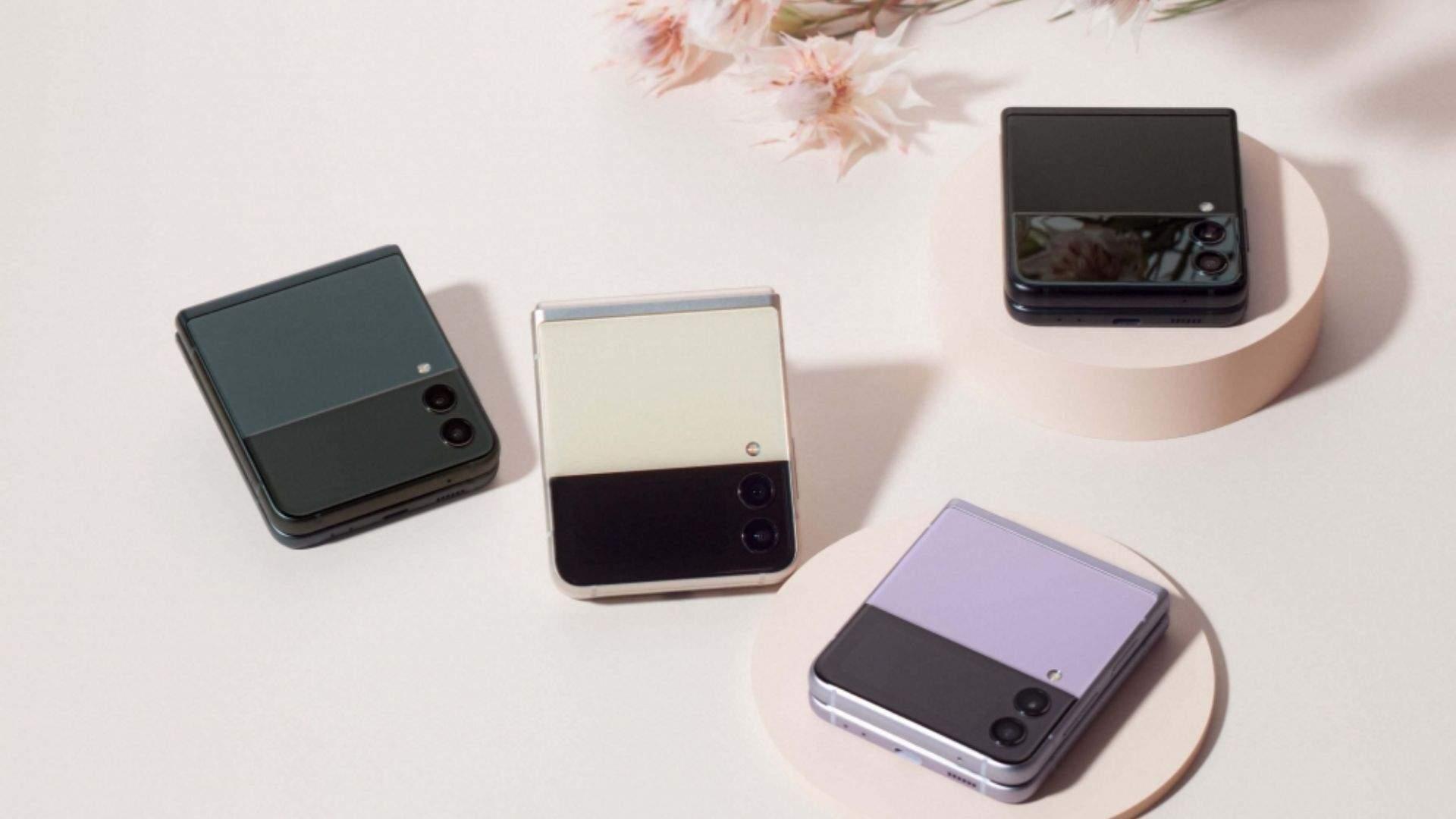Quatro celulares Galaxy Z Flip 3 de cores diferentes fechados em fundo rosa