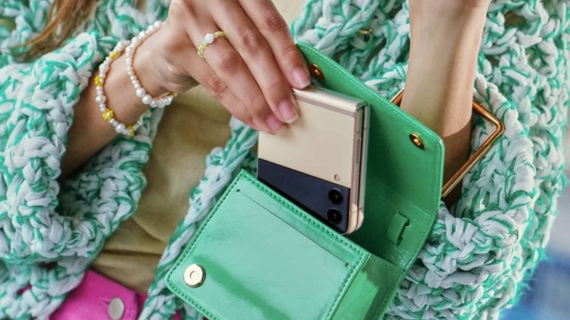 Mulher coloca o celular Galaxy Z Flip 3 cor creme dentro de uma bolsa verde