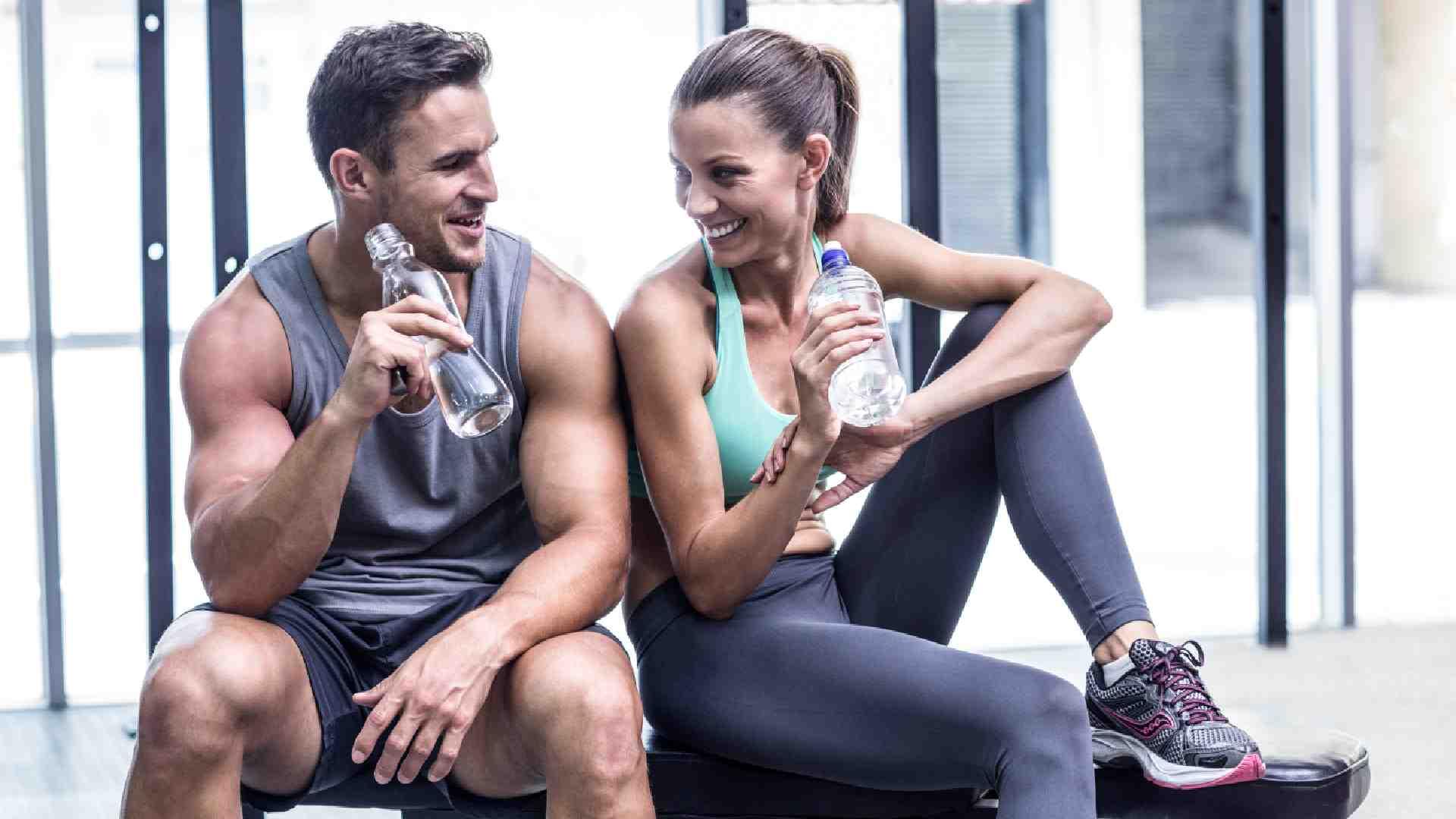 Homem e mulher bebendo água na academia