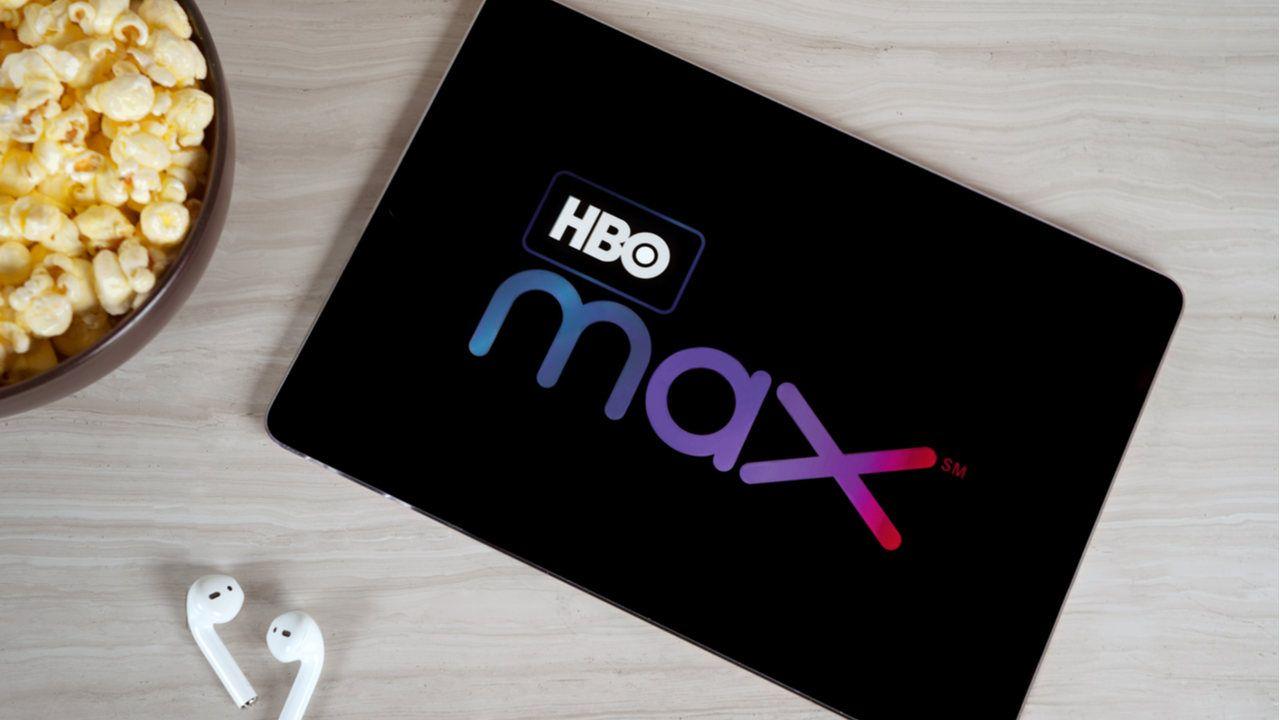 Tablet sobre mesa de madeira na tela inicial do HBO Max. Fones de ouvido bluetooth e pote de pipoca no canto da foto.