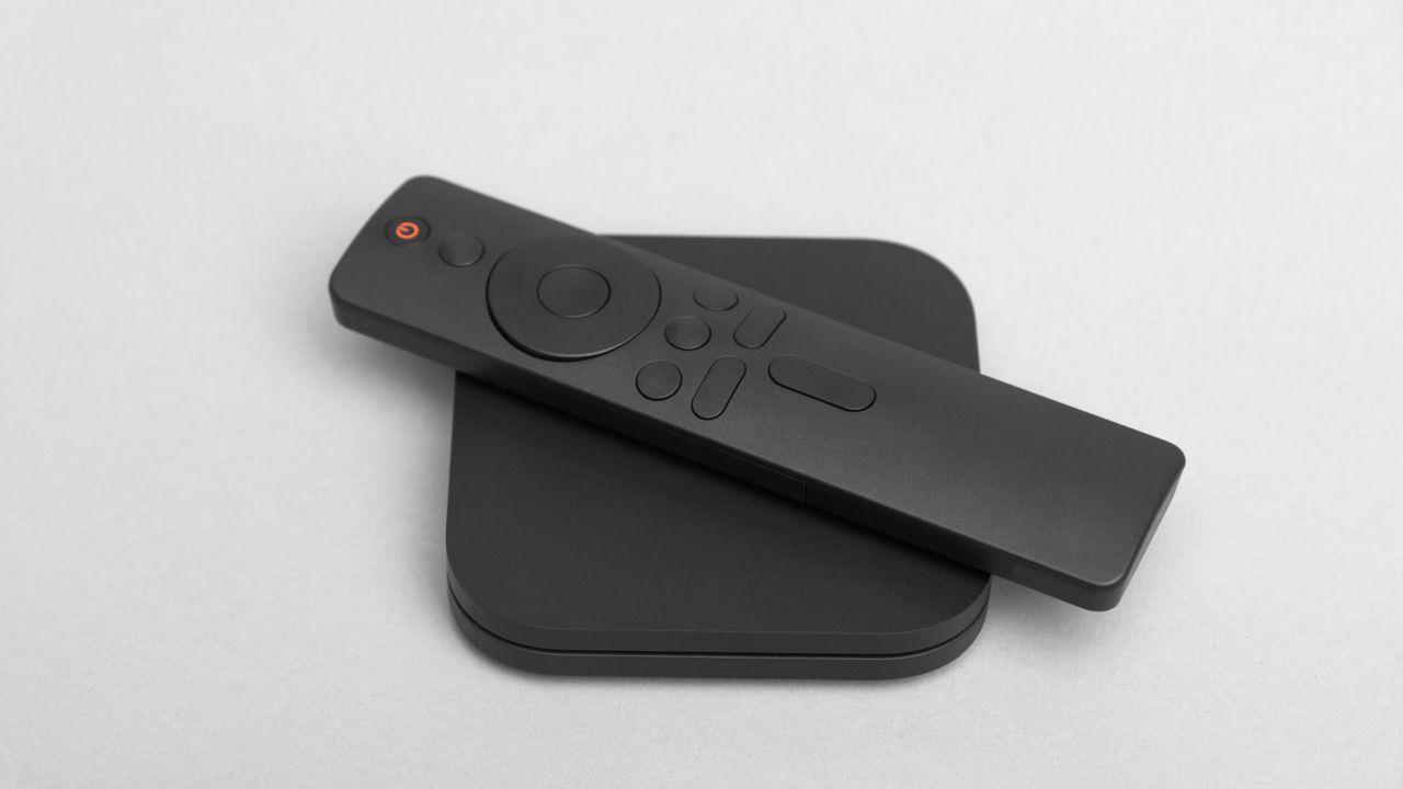 TV box com controle remoto em cima, tudo sobre superfície cinza.