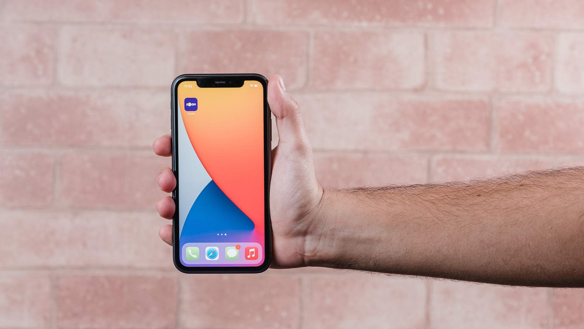iPhone 11 com tela acesa sendo segurado por uma mão em fundo de tijolos