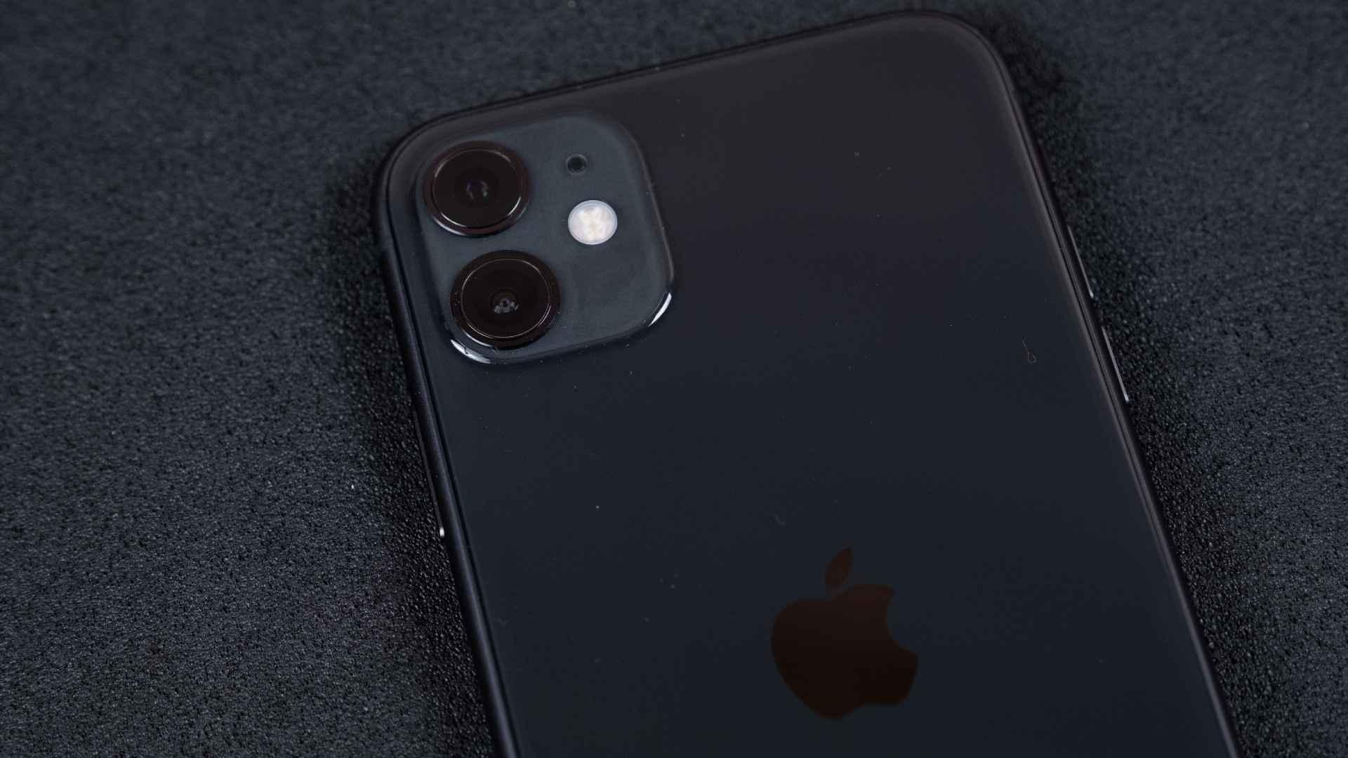 Detalhe da traseira do iPhone 11 preto, mostrando a câmera dupla, em fundo preto