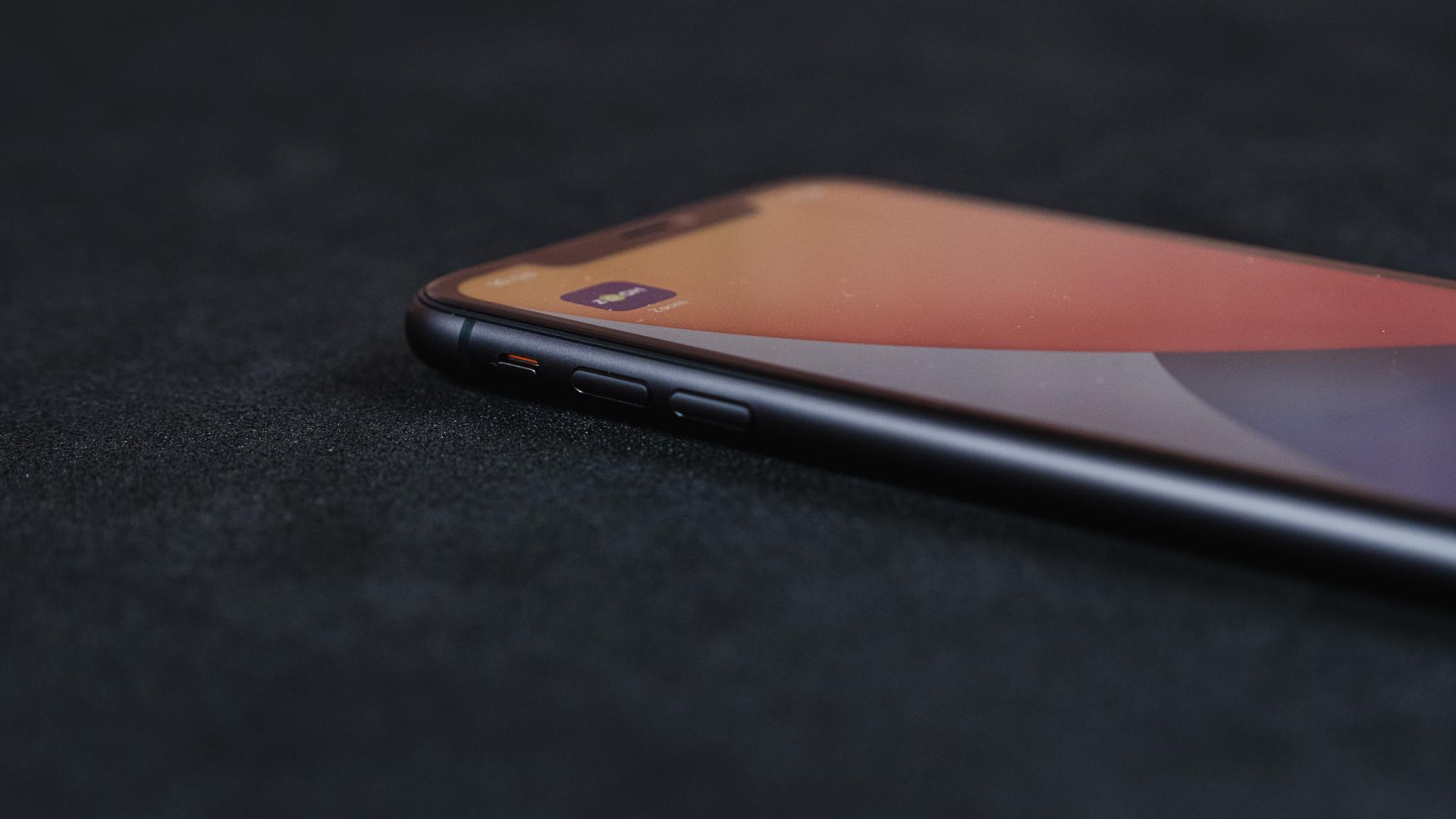 Lateral esquerda do iPhone 11, com destaque para os botões, em um fundo preto