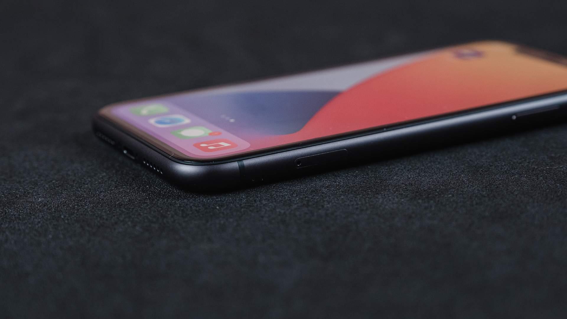 Lateral do iPhone 11, feita em metal, em um fundo preto