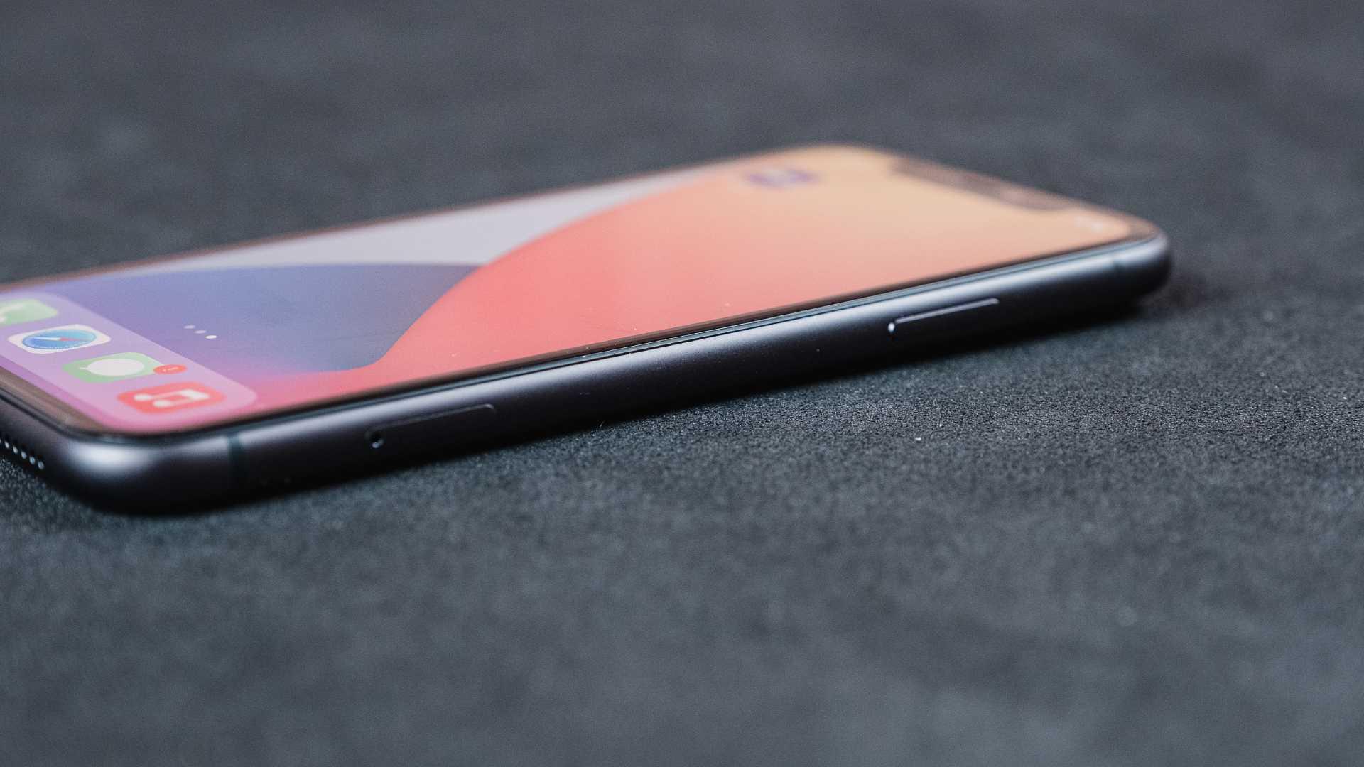Detalhe da lateral direita do iPhone 11, com botão de bloqueio, em um fundo preto