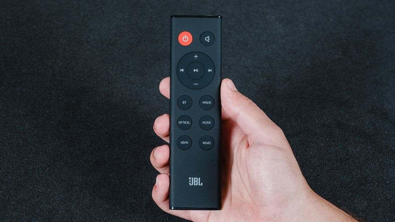 Mão segura o controle remoto da soundbar JBL SB160