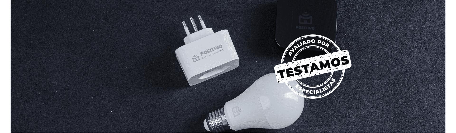 """Lâmpada smart, tomada e smart controle universal apoiados em superfície cinza, com selo """"Avaliado por Especialistas""""."""