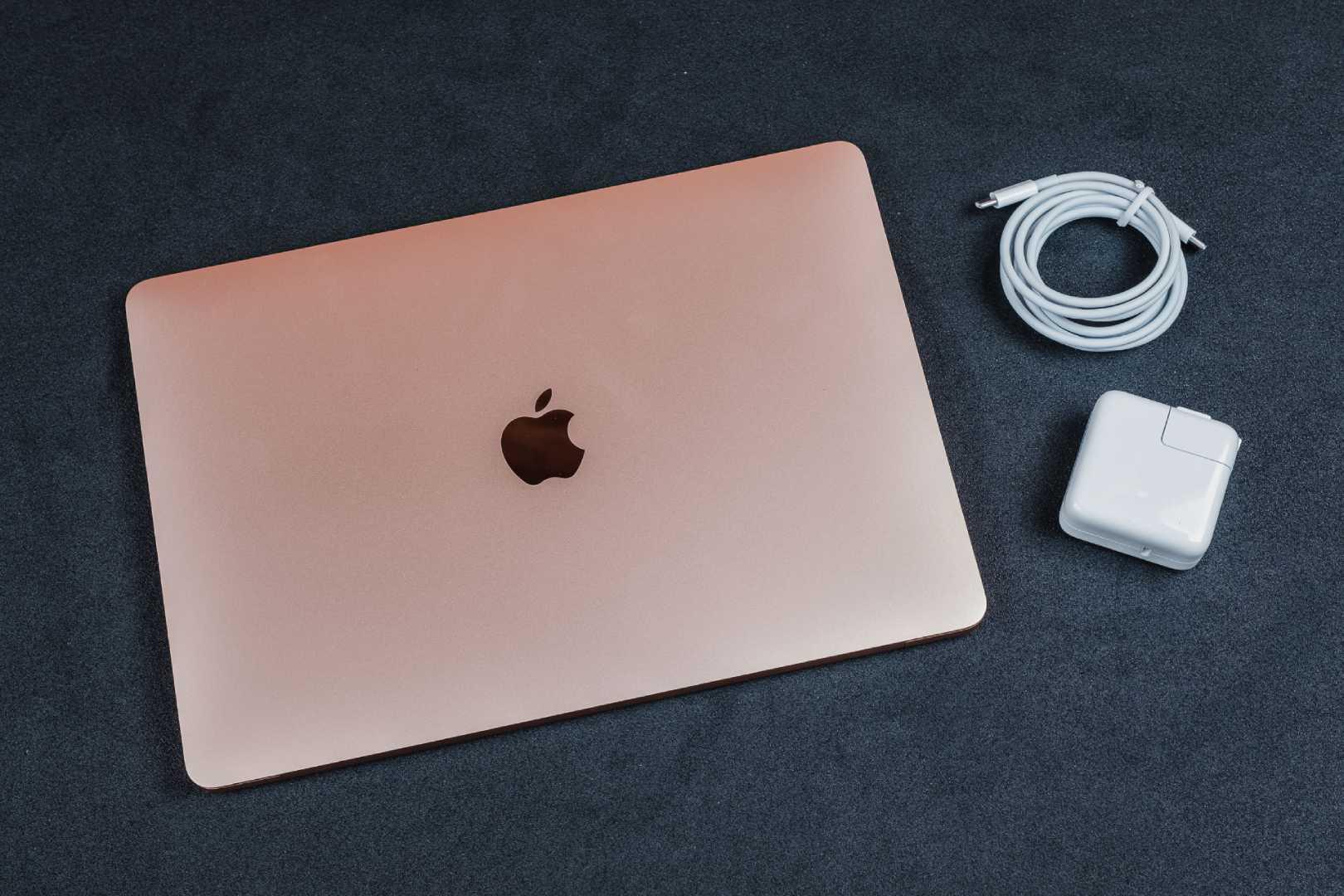 MacBook Air rosa, cabo e carregador sobre mesa preta