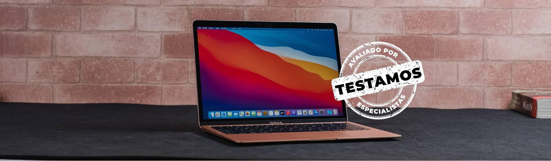 """MacBook Air M1 sobre mesa preta com selo branco escrito """"Testamos: Avaliados por Especialistas"""""""