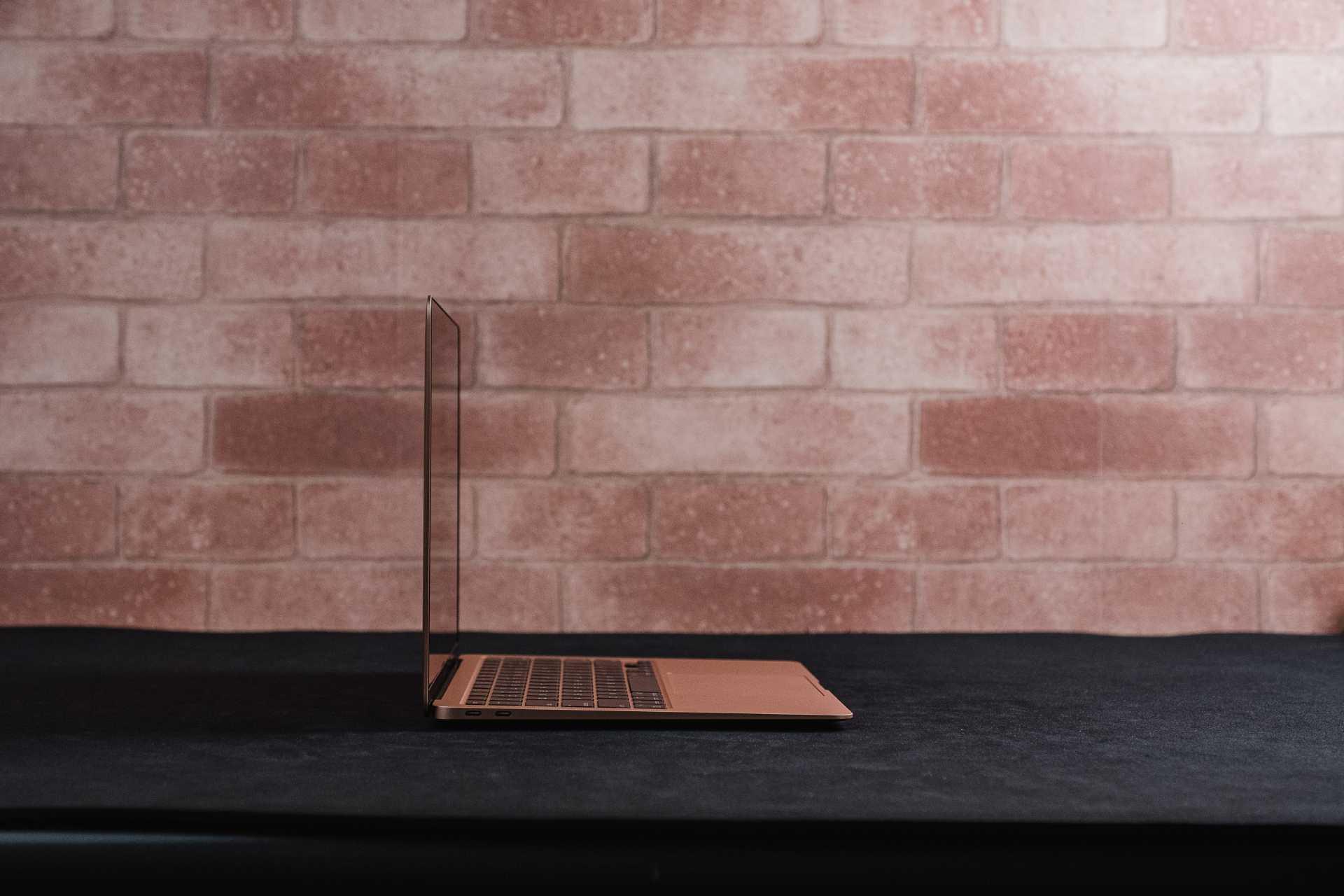 MacBook Air M1 de lado sobre mesa preta