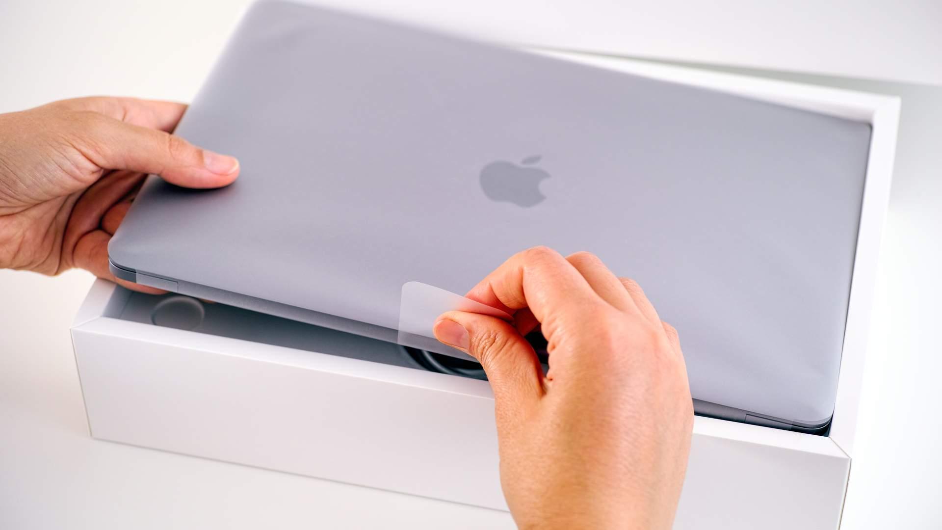 MacBook novo sendo tirado de caixa original branca