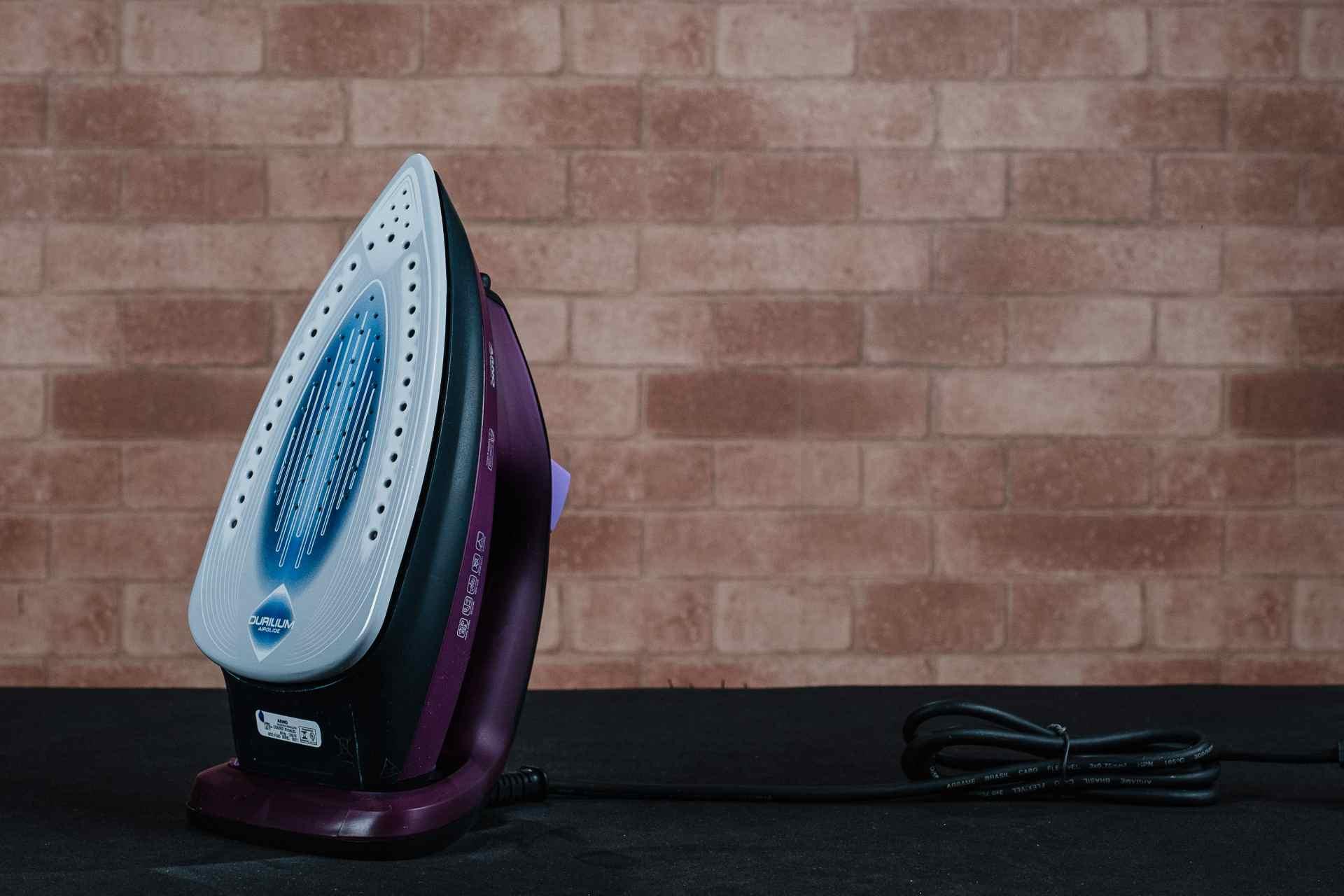 Foto do ferro de passar roupas na em pé com a base prateada com detalhes azuis virada para a frente