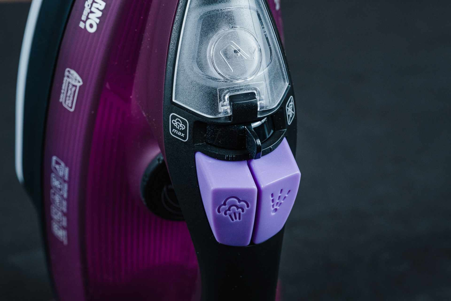Detalhe do ferro de passar roupas na vertical mostrando uma tampa transparente branca, um seletor preto e botões em lilás