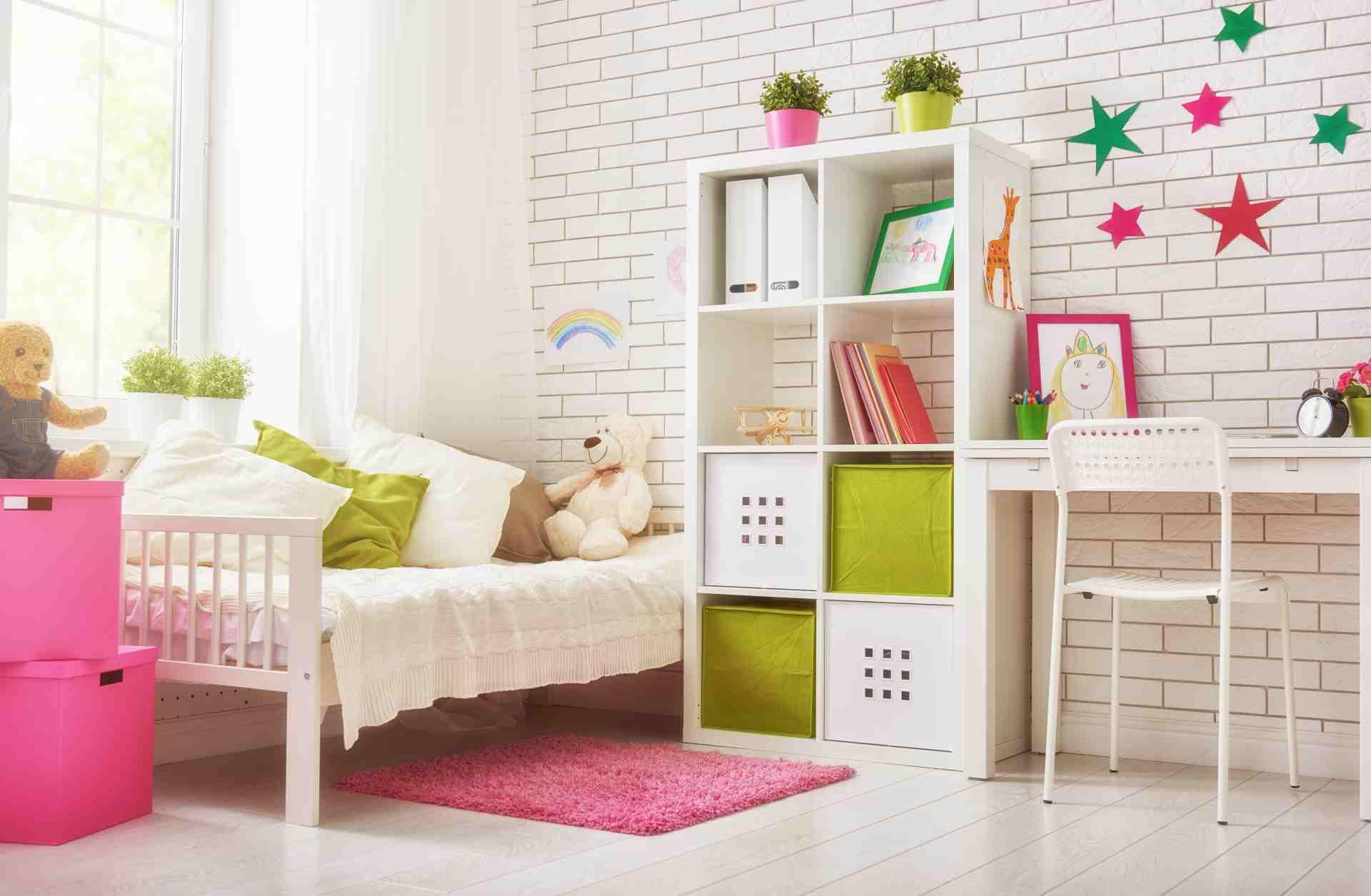 Quarto infantil com cama com travesseiros e ursinho de pelúcia, estante e escrivaninha