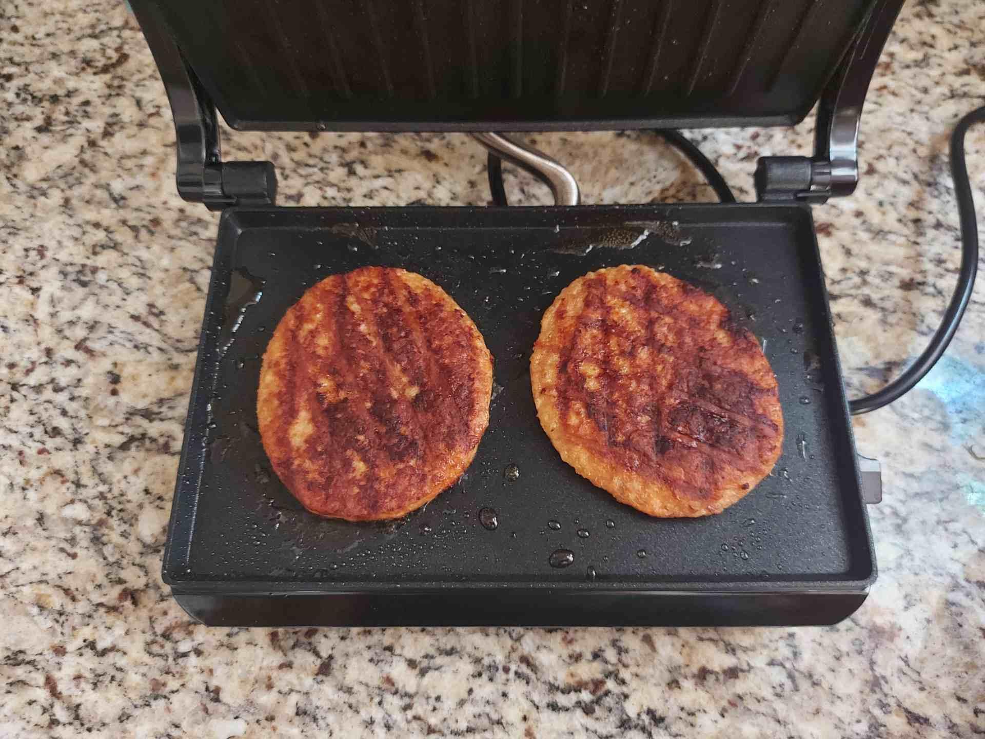Imagem de dois hambúrgueres grelhados na chapa preta da sanduicheira
