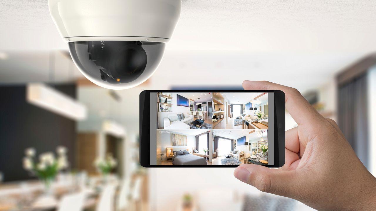 Câmera de segurança Wi-Fi instalada no teto, com um celular aberto no monitoramento em tempo real dos cômodos.