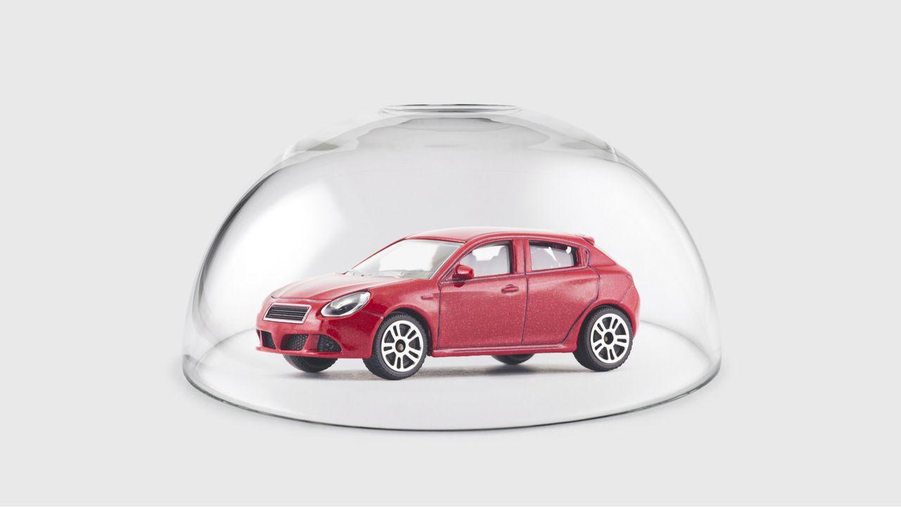 Carro vermelho protegido por cúpula de vidro em fundo branco