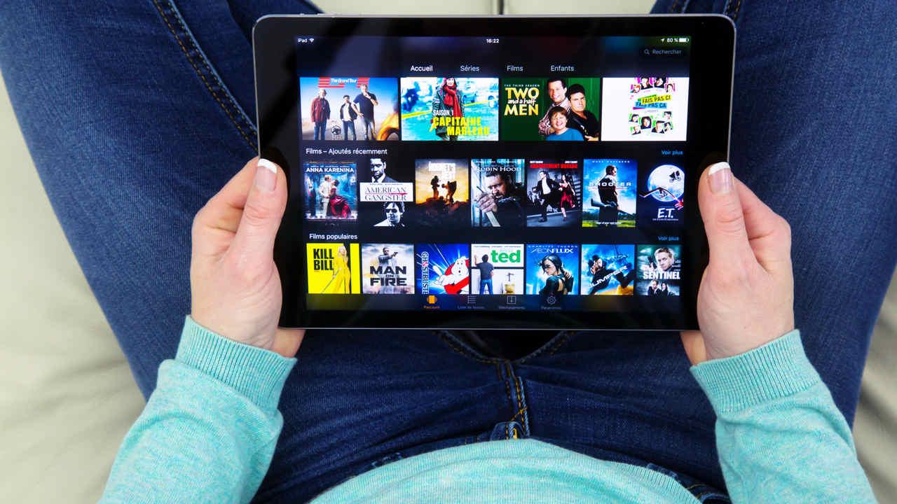 Catálogo de séries do Amazon Prime Video aberto em um tablet, enquanto mãos o seguram.
