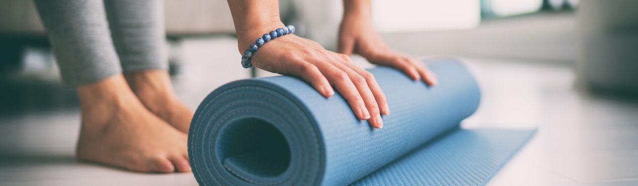 Mãos de mulher enrolando um tapete de yoga azul