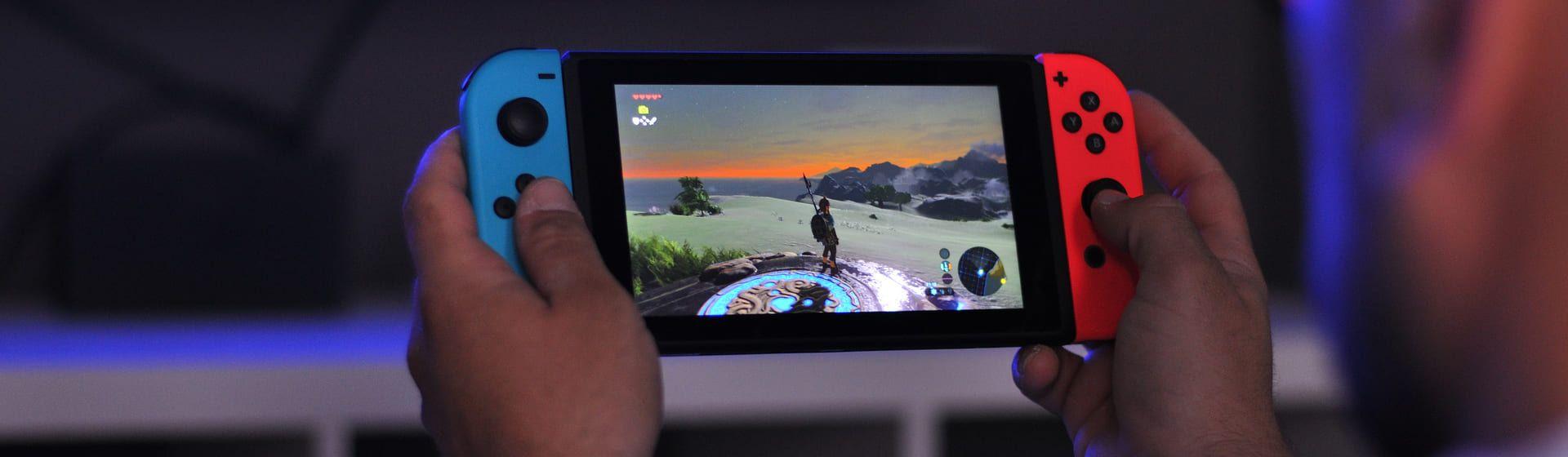 Duas mãos segurando um videogame portátil Nintendo Switch