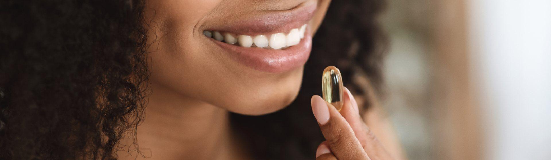 Mulher negra segurando um comprimido de vitamina